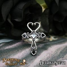 Alchemy Gothic AG-R211 Amourankh ring  A pewter ring of an ankh fashioned of scrollwork heart motifs, ending in three small black enamelled hearts on each arm and a Swarovski black diamond, starlet-shaped crystal at its centre.