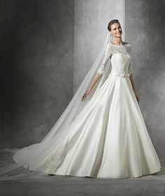 Simple princess wedding dress in mikado silk with long sleeves. Lace bodice with bateau neckline and sheer overlay with sweetheart neckline. Mikado silk belt with a bow center front and back. Mikado silk princess skirt.