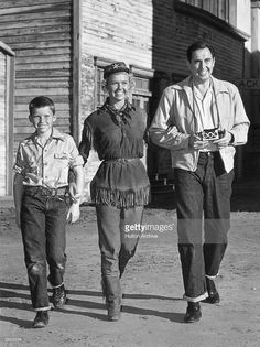 1953: A full-length image of American actor Doris Day walking with her son, Terry, and her husband, Marty Melcher, who is holding a Stereo Realist camera, during their visit with her on the set of director David Butler's film, 'Calamity Jane'. Day is in costume as the title character. She is wearing a fringed suede top, matching suede pants, fringed suede boots, an army cap, and a bandana.