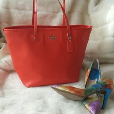 Coach zip top tote This is such a vibrant coral color I mean gorgeous fully lined with the same color lining this is an authentic Coach zip pockets on the interior used a few times beautiful bag 16 inches wide x 11 height Coach Bags Totes
