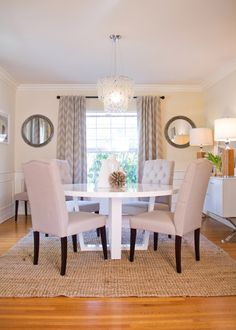 Dining Room with round white table, neutral tufted chairs, modern white sideboard with silver x-legs, round mirrors, sisal rug, wainscoting, pretty chandelier and chevron curtains - West LA home by Vanessa De Vargas of Turquoise Interior Design