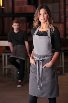 The Soho bib apron. Frost/Grey colour. The perfect combination of edgy fashion and forward-thinking functionality. Featuring a contrast color block, buttoned neck strap, reinforced stress points and two patch pockets. Perfect for any kitchen, cafe or restaurant.