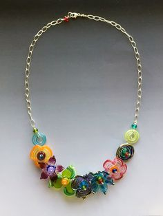 GLASS NECKLACE - SECRET GARDEN COLLECTION Handmade lampwork glass bead and sterling silver necklace featuring colorful glass accented with silver highlights made with a reactive iridescent glass. This lovely necklace is composed of SRA artisan crafted lampwork playful organic