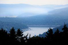 Im Nationalpark Eifel scheint die Landschaft unberührt. Dass sich die Rur hier zu einem langen See aufstaut, ist zwar Menschenwerk, erhöht aber den Reiz der Landschaft noch. Mit Ausflugsbooten kann man hier in engen Kurven durch die Berge tuckern.