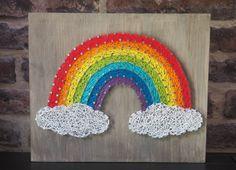 Arc en ciel et nuage, réalisé avec la technique du string art ou encore du fil tendu. Il est sur un support en bois teinté effet vieilli de taille 30/25 des pointes en acier poli et du fil pour crochet blanc, rouge, orange, jaune, vert, bleu, indigo et violet.