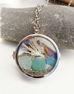 Glass Beach in a locket! Lovely aqua and amber beach glass with California Beach sand and dried white ocean kelp.   Rhodium chain 18 inch and loose sea glass.Locket Pendant is glass.1 inch diameter.