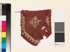 Textile fragment from a tab with a cross, shield-shape, and linked crossesfront | Near East 10th - 15th century | cotton, dyed red, and embroidered with white flax