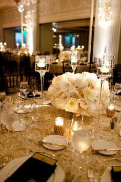 OR, gold overlays on white linen, white napkin dinner shirt fold w/ black bow tie for the men & rose fold for the ladies