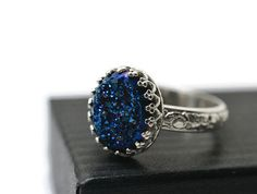This gothic blue druzy statement ring will be made to order within 7 business days. A signature may be required upon delivery. The druzy is 12mm x 10mm set in a sterling crown bezel cup. The ring band is 3.4mm wide with a repeating floral pattern. This ring has been oxidized, but if you prefer a shiny finish as in photo 5, please select that option from the drop down menu.  Oxidization isnt a permanent finish but we provide care instructions to preserve and reapply it if necessary.  Please…