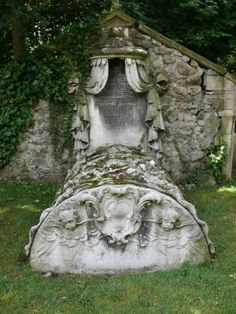 "A bed monument from a small churchyard in Essex UK. The ""sheets"" of the bed depict many symbols including a book, some skulls, bones, and an Ouroboros (a snake biting its own tail and forming a circle, thus symbolizing eternity.)"