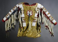 A BLACKFOOT BEADED AND FRINGED HIDE MAN'S SHIRT    composed of hide, red wool cloth, glass beads, twisted wool yarn, sinew, thread, and ermine, the hide painted in black pigment with a series of dots.  Length 29 1/2 in. Click to enlarge: http://assets7.pinimg.com/upload/137641332332888761_Y0nH3d9C.jpg
