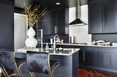 Slate gray cabinetry and glossy hide-upholstered bar stools helps to transform a modern kitchen into a luxurious cooking space. Designed by Lee Kleinhelter, Lonny June 2013.