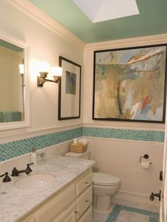Bathroom With Blue Mosaic Tile Accents  This bathroom has color to spare thanks to a beautiful blue mosaic tile border, a pattern which is repeated on the floor. The ceiling carries the same hue, which is complemented by artwork hanging on the walls.