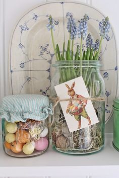Spring flowers in a jar with pastel eggs in another.