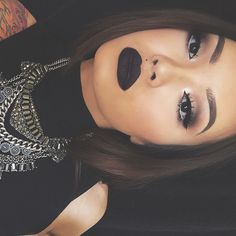 Light, smokey eye and black lip. Love the statement necklace as well.
