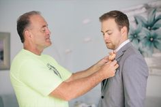 groom putting on boutonniere