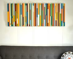 These old sticks of wood were turned into a wall art masterpiece with the help of some colorful paint!