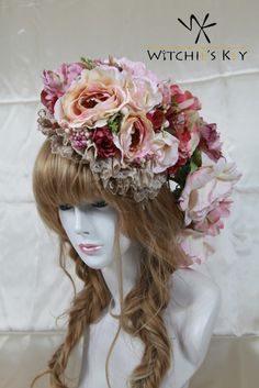 淡い暖色系のお花に動物が隠れたヘッドドレス。後ろに花が垂れ、花のポニーテールがあるように見えるデザイン