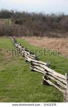 stock photo : A split-rail fence runs down a hill next to a field, to a streambed, then up a hill in the distance