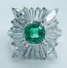 This fascinating vintage piece is crafted in solid luxurious 14K white gold. Featured in the center is a genuine earth mined Colombian Emerald
