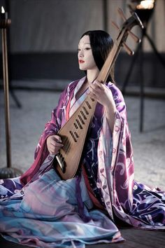 Asian Woman playing an instrument
