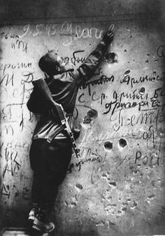 A Soviet soldier writes graffitti over the walls of the Reichstag. Berlin, 1945. Anatoly Morozov