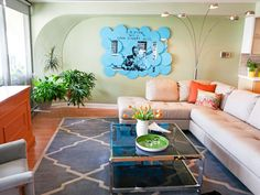 Pale+green+walls+are+complemented+by+blue+and+orange+decor+in+this+eclectic+living+room.+Anchored+by+a+large+upholstered+sectional+and+a+plush+gray+rug,+this+mod+space+mixes+contemporary+and+retro+accessories.