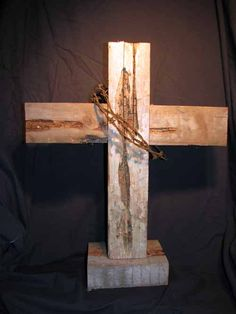 Rustic cedar cross with barbed wire.
