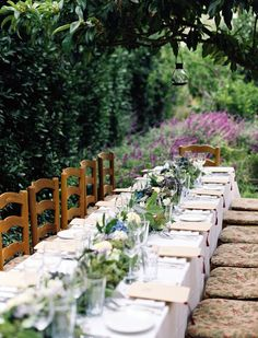 Long tables set in the garden. Add twinkle lights and this is dreamy scene for the reception.