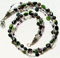 Maggies Beadery 25 inch multi-strand green, gray and silver beaded necklace. This closes with a large Tibetan Silver flower lobster clasp.