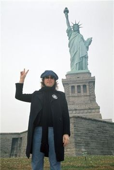 John Lennon standing in front of the Statue of Liberty.