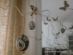 The branches were created by folding the simple metal hangers with pliers, simulating twisted branches  My husband advised me to leave the metal to contrast between different materials.    The eggs are real eggs, empty and painted with acrylic plaster and decorated with a simple black marker. The hook for hanging I did with string.