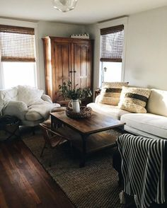 """Neutral toned living room setting that looks more """"real"""" than magazine styles (pillows, striped blanket, and basket)"""