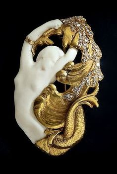 Art Nouveau Mermaid Brooch. A sea nymph carved in African ivory, or perhaps, écume de mer, is frolicking and rollicking in golden waves and rose-cut diamond sea foam. This art nouveau dream is magnificently executed in rich 18k yellow gold and is in fine condition except for one tiny break on the mermaids arm which has been cleverly concealed with a golden arm bracelet.