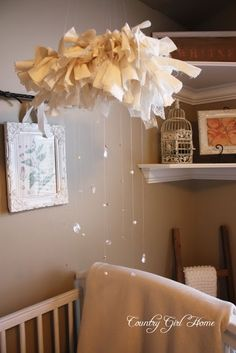DIY mobil - Use a wooden wreath form (Dollar Tree) and tie strips of fabric and lace around it. Then, tie beads to different sizes of fishing line to complete the look!