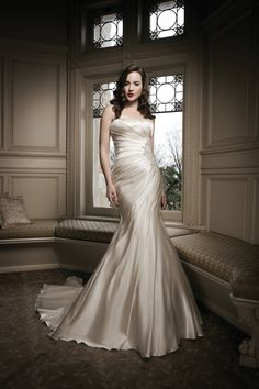 Champange color, fit and flare wedding dress with jeweled accent by Justin Alexander