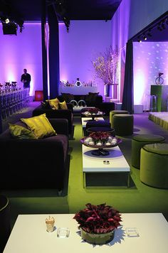 A chic wedding reception lounge showcases purple and green velvet couches and lavender colored uplighting.