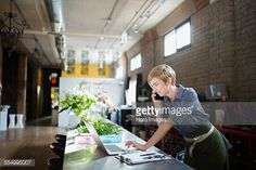 Stock Photo : Florist working at laptop in flower shop