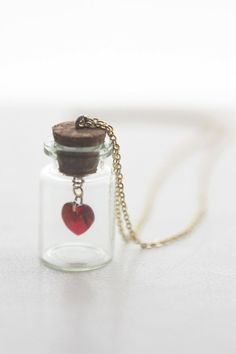 Beautiful red heart crystal Swarovski in a glass bottle Keep your heart and love in this small bottle around the one you love! A great Valentines, wedding, anniversary or just because gift ... Heart measures 10x10mm Jar measures 35x22mm excluding cork Chain measures 16 inches with a 2