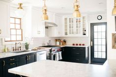 In this kitchen, black and white cabinets are punctuated with brass hardware and white subway tile.