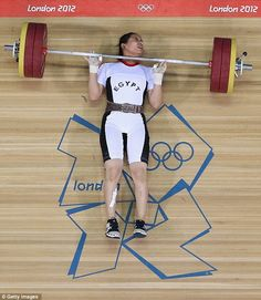 Pinned: Egypt's Khalil Mahmoud Abir Abdelrahman is pinned to the ground by the 151kg wights after she fell during a lift in the 75-kilogram event