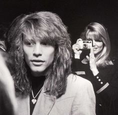 Photographer Christie Brinkley backstage with Jon Bon Jovi in 1990. Turn the camera around sweetheart, it's you everyone wants to look at.