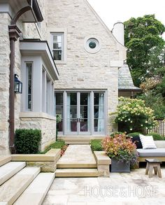 How To Bring Glamor To Your Backyard- This home's façade, made of Indiana cut limestone and rubble stone, is a cohesive backdrop for elegant patios and paths.