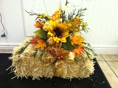 silk flowers nicely arranged on a small hay bale...This would make great decorations for an outdoor fall country wedding...jodie