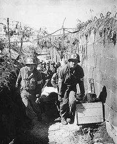 US Army medics removing a casualty from the battlefield to an aid station in an air shelter, near Brest, France, 28 Aug 1944 (US National Archives)