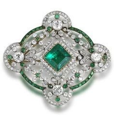 A Belle Époque emerald and diamond brooch/pendant, circa 1910. Set to the centre with a square-cut emerald and single-cut diamond cluster, to an openwork border set with swags and floral garlands, within a quatrefoil frame, millegrain-set throughout with single and brilliant-cut diamonds and calibré and circular-cut emeralds, diamonds approximately 4.80 carats total, detachable brooch fitting. #BelleEpoque #Pendant #brooch;  sold 31,651 USD;  25/4/12.