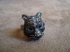 Anel em metal na cor prata velha no formato de tigre com aplicação de cristal Swarovski branco e preto.  Anel regulável. R$42,00