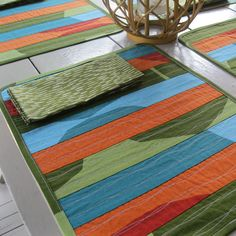 """This contemporary, placemat/napkin set of four will top your table in bold style. Three colors of Marimekko """"Kivet"""" are stitched and quilted to form beautiful color blocks of pattern in green, blue and orange. Kivet is Finnish for """"stones"""" and you will love the movement of the print with large, irregular curved lines. Marimekko """"Sade"""" is used for the placemat backing and the cloth napkins."""