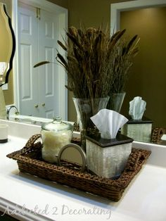 Great bathroom idea. Cattails and dried grasses in a tall vase, cosmetic puffs in a jar and a mother-of-pearl tissue box.