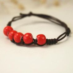 Shaolin unisex rope bracelet with red beads and dark brown cords.